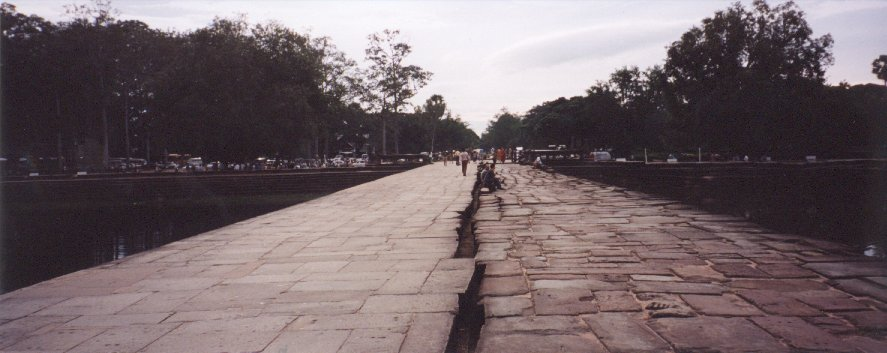 This photo was taken as we left Angkor Wat, and shows the causeway over the moat. The left hand side of the causeway and the left bank of the moat, were reconstructed by the French archeologists who restored the site before the war in Cambodia. The right hand side has been left to show the condition of the monument before restoration.