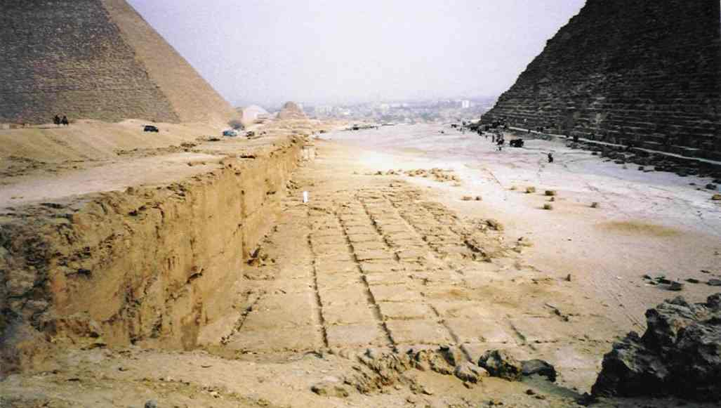 This picture shows what is believed to be the quarry where blocks were cut for the construction of Khafre's pyramid, which is visible on the right. Khufu's pyramid is on the left, with the city of Cairo in the distance.