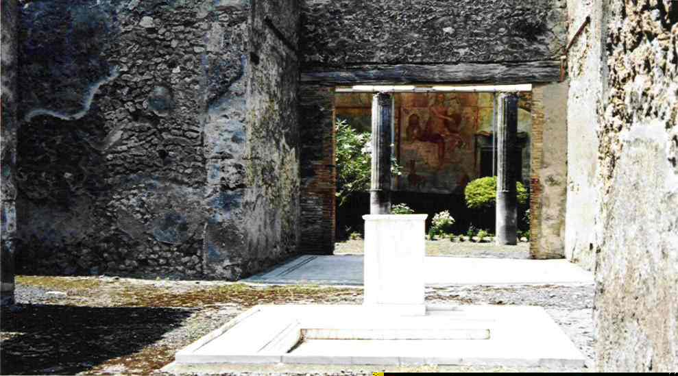 This is a view looking through, into a courtyard with a quite modern looking water feature. Behind the pool you can see a floor mosaic, and beyond that, there is a mural on the wall. Many of the villas and houses of Pompei had courtyards with a pool designed to catch rainwater.